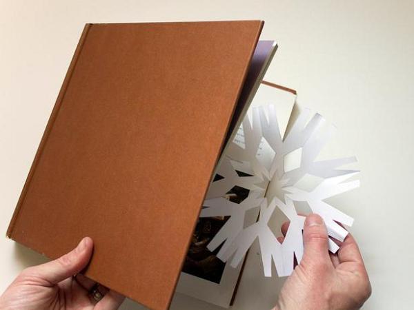 расправляем снежинку из бумаги в книге