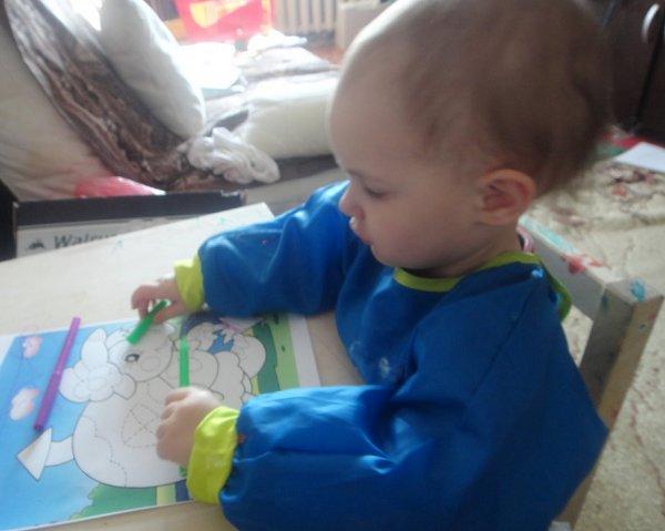 ребенок раскрашивает разными цветами